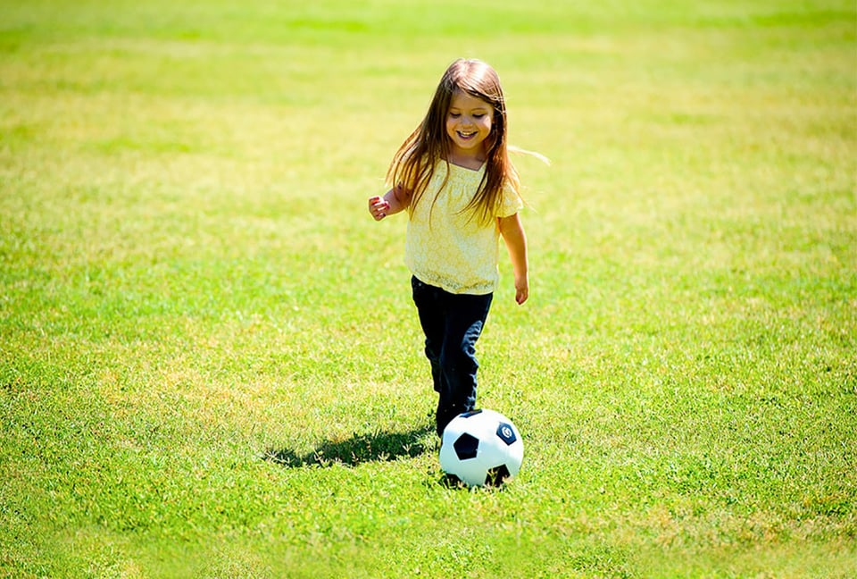 サッカーボールを追いかける女の子